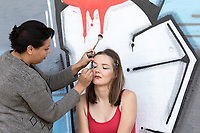 Make-up artist putting eye shadow on a Model. Model with eyes closed. Background colored concrete wall