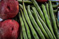 Fresh, crisp green beans and new red potatoes are paired in an offering at a farmers market in July.