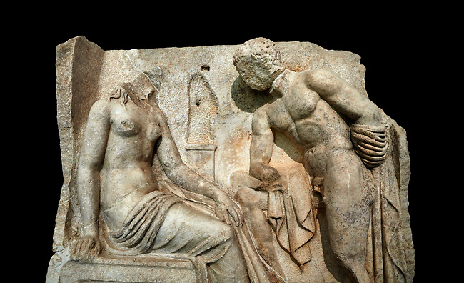 "Close up of a Roman Sebasteion relief  sculpture of Io and Argos Aphrodisias Museum, Aphrodisias, Turkey.   Against a black background.<br /> <br /> A powerful hero is folding a sword gazing closely at a half naked and dishevelled young heroine who sits on a chest like stool. Between, on a pillar base stood a small, separately added statue of a goddess ( now missing). The scene follows a scheme used in the relief panels ""Io guarded by Argos"". Io was one of Zeus's lovers, and Argos was a watchful giant sent to guard her by Hera, Zeus's wife."