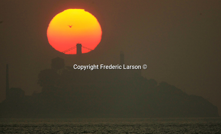 The rising sun sihouetted one of the tops of a towers the Bay Bridge and Alcatraz Island as it slowly appeared out the low lying fog and haze Saturday morning off the San Francisco Bay in California.