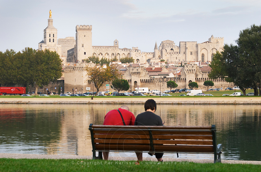 Pope's Palace in Avignon and the Rhone river with the Palace reflected in the water surface of the river. A young couple man and woman sitting on a park bench facing the palace, wearing a red shirt and a black shirt Avignon, Vaucluse, Provence, Alpes Cote d Azur, France, Europe