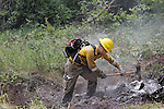 SPEARFISH, SD - JULY 1, 2016 -- A member of the North Haines Volunteer Fire Department of Rapid City, S.D. carries out mop-up efforts along Higgins Gulch Road at the Crow Peak Fire Friday afternoon west of Spearfish, S.D.  (Photo by Richard Carlson/dakotapress.org)