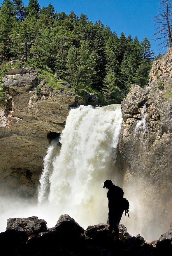 A hiker is silhouetted in front of Natural Bridge Falls near McLeod, Montana.