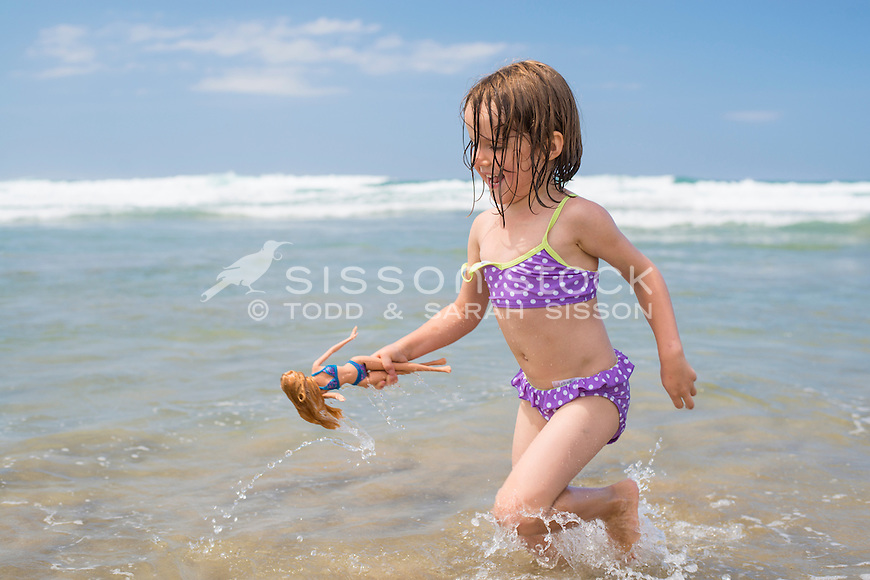 Young girl happily playing in the waves at the beach on a summers day, Whangarei Heads, Northland, New Zealand - stock photo, canvas, fine art print