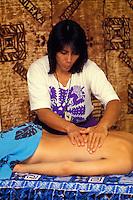 Hawaiian woman giving a lomilomi massage with kapa cloth hanging behind her