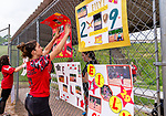 WOLCOTT, CT. 10 June 2020-061020BS16 - Wolcott Girls Softball player and teammate, Freshman Mayci Abou Arrage, left, helps hang a photo collage of one of the seniors as they honor the Wolcott Girls Softball team seniors at the Wakelee Elementary School field on Wednesday. Bill Shettle Republican-American