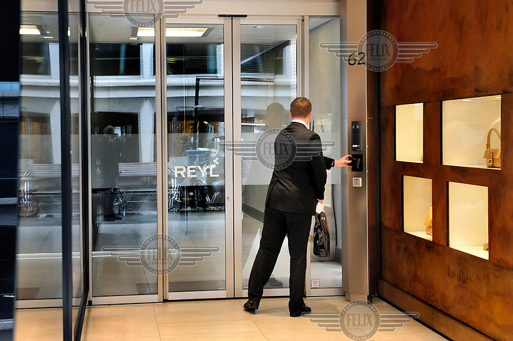 A businessman enters Reyl & Cie banking offices in Geneva.