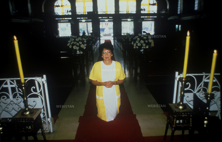 Philippines. Manila. 1986. Cory Aquino, opponent of President Marcos, praying inside a church. Philippines. Manille. 1986. Cory Aquino, opposante au Président Marcos prie dans une église.