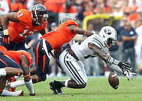 Brigham Young running back Jamaal Williams (21) fumbles then recovers the ball next to Virginia safety Anthony Harris (8) and Virginia linebacker Daquan Romero (13) during the first half of the game in Charlottesville, Va. Virginia defeated Brigham Young 19-16. Photo/Andrew Shurtleff