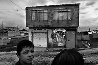 A displaced boy from Meta department plays in front of a brick house in the slum of Ciudad Bolívar, Bogota, Colombia, 30 May 2010. With nearly fifty years of armed conflict, Colombia has the highest number of civil war refugees in the world. During the last ten years of the civil war more than 3 million people have been forced to abandon their lands and to leave their homes due to the violence. Internally displaced people (IDPs) come from remote rural areas, where most of the clashes between leftist guerrillas FARC-ELN, right-wing paramilitary groups and government forces takes place. Displaced persons flee in a hurry, carrying just personal belongings, and thus they inevitably end up in large slums of the big cities, with no hope for the future.