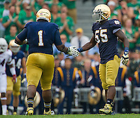 Nose tackle Louis Nix (1) celebrates with linebacker Prince Shembo (55).