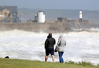WINDY WEATHER WALES<br /> Pictured: A young couple stroll as waves batter the promenade wall of the lighthouse in Porthcawl, south Wales, UK. Tuesday 06 June 2017<br /> Re: Strong winds have been affecting parts of the UK
