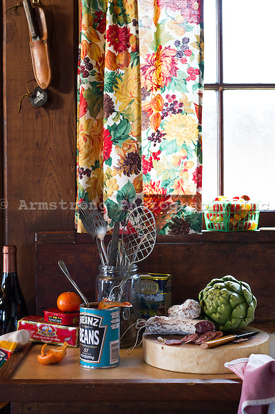 Kitchen countertop in a rustic cabin and a window with floral curtains. On the counter are an open can of Heinz beans, tinned fish, olive oil, kitchen utensils, cutting board with sliced salami, an artichoke, a bottle of wine, knife, and cherry tomatoes.