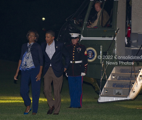 United States President Barack Obama, accompanied by First Lady Michelle Obama, walks away from Marine One upon their return to the South Lawn of the White House in Washington on October 17, 2010.   .Credit: Mannie Garcia - Pool via CNP