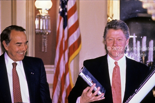 """United States President Bill Clinton, right, shows off a big """"Veto Pen"""" and a book presented to him by U.S. Senate Republican Leader Bob Dole (Republican of Kansas) at a U.S. Senate Republican Policy luncheon in Washington, D.C. on March 2, 1993..Credit: Jeff Markowitz / Pool via CNP"""