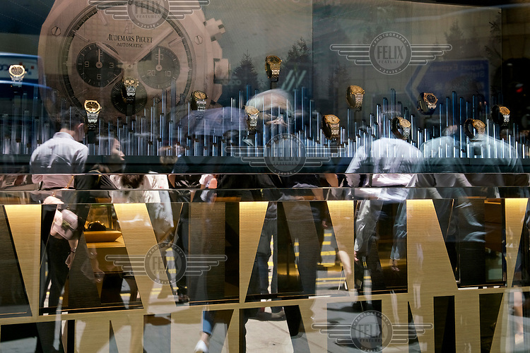 People reflected in the window of a watch shop in the 'Central' financial district.