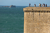 Tourists looking out to sea from the top of Bidouane Tower, Saint Malo, Brittany, France.
