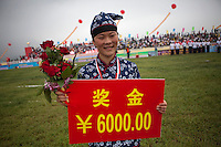 A female competitor dressed as a revolutionary volunteer holds her winners cheque at the Red Games. Held in Junan County, this sporting event is a nostalgic tribute to the communist era.