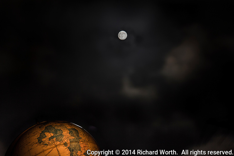 An old globe and a full moon, the Full Strawberry Moon of June, with clouds rushing by, trying to spoil the photo.