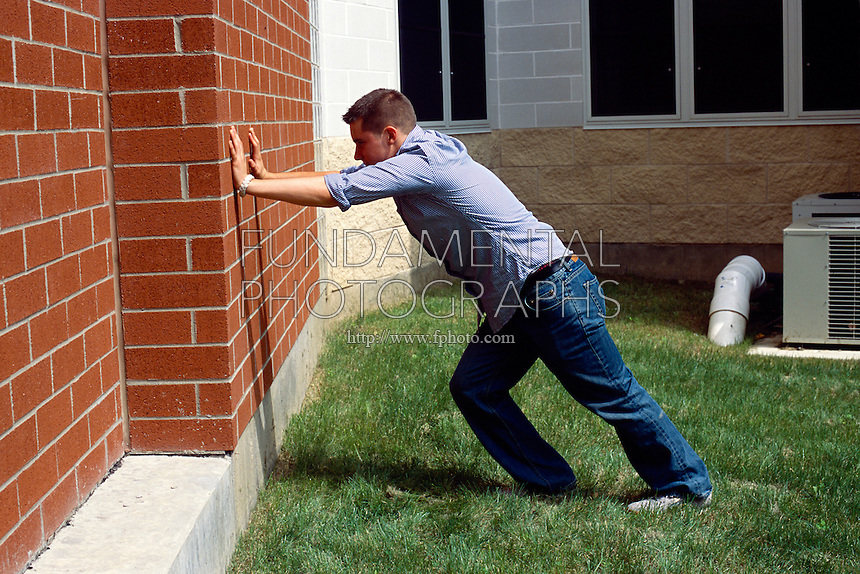 NEWTON'S THIRD LAW<br /> A Young Man Pushing Against A Wall<br /> The third law states that for every force there is an equal and opposite force. If one pushes a wall, the wall will push back with equal force.