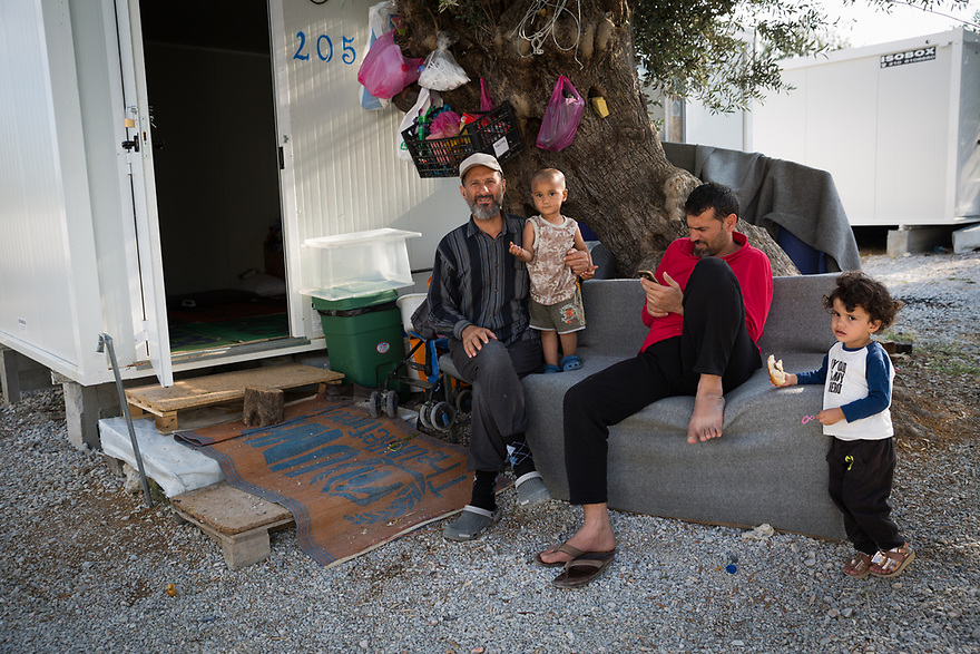 Three generations of Iraqi refugees at Iraqi refugee with his grandchild at Kara Tepe Site on the Greek island of Lesvos, where hundreds of refugees are accommodated as they wait to their procedure.