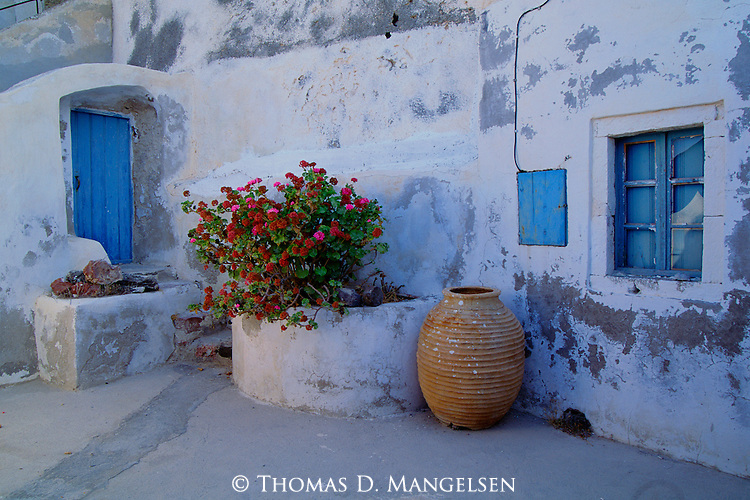 A geranium sits between a blue door and shuttered window on Santorini Island in Greece.