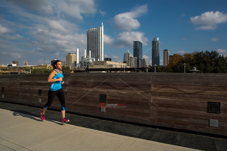 Fit young Woman Athlete Running on the Lamar Pedestrian Bridge with Austin, Texas Skyline on a bright, sunny day.
