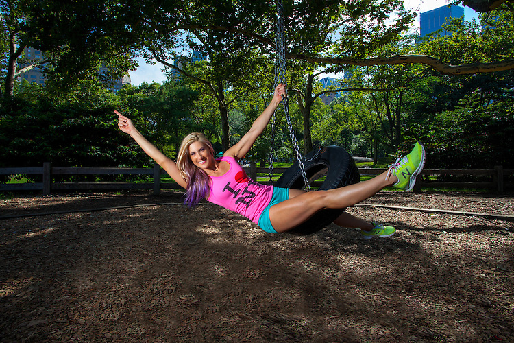 Young Blonde Athletic woman sitting and rocking on a tire swing in Central Park