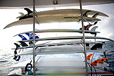 INDONESIA, Mentawai Islands, Kandui Resort, surfboards stacked in a rack on the back of a surf boat