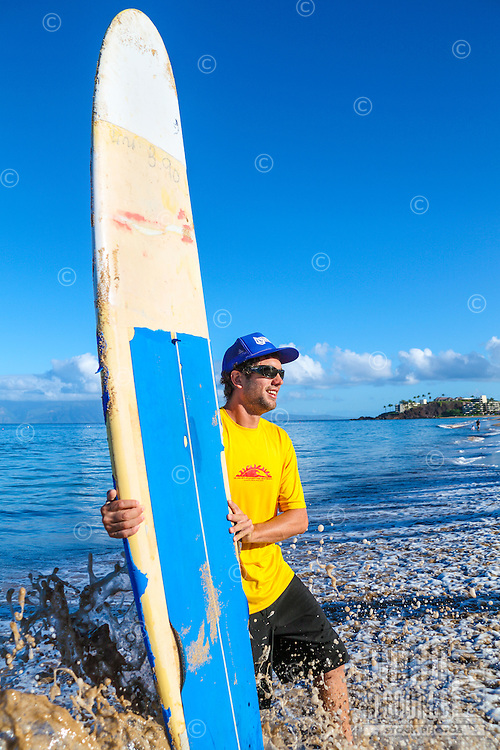 A surf instructor holds a surfboard at Ka'anapali Beach, Maui.