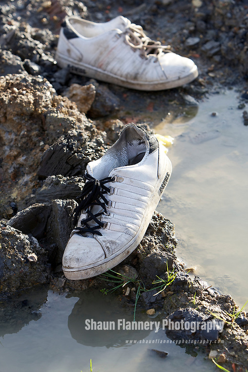 Pix: Shaun Flannery/shaunflanneryphotography.com...COPYRIGHT PICTURE>>SHAUN FLANNERY>01302-570814>>07778315553>>..27th January 2012……………..Discarded trainers sit on a mud and water filled construction site.