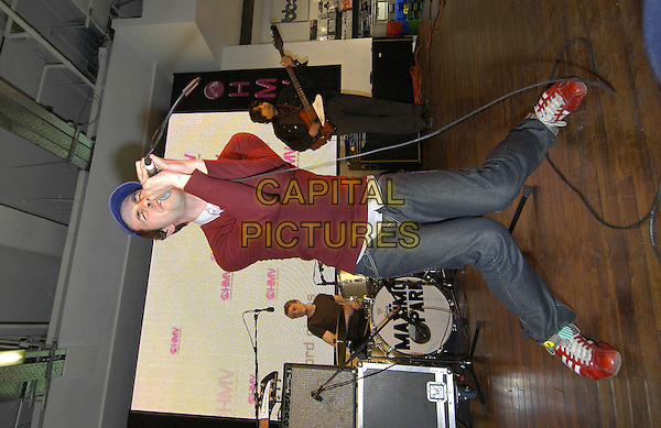 MAXIMO PARK.Perform live gig during an Instore Signing Session, .HMV Oxford Street, London, May 17th 2005..full length concert funny legs pose.Ref: HT.www.capitalpictures.com.sales@capitalpictures.com.©Capital Pictures