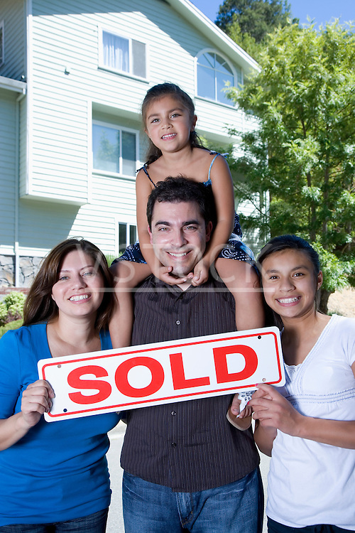 "Portrait of family with two girls (8-9, 14-15) holding ""Sold"" sigh in front of house"
