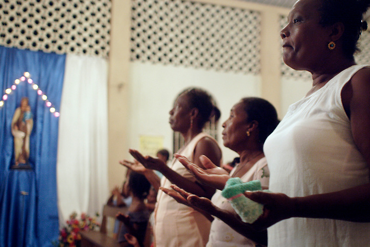 NUQUÍ, EL CHOCO, COLOMBIA -- DECEMBER 11:  Parishioners pray during a Catholic church service in Nuqui on December 11, 2005. Nuquí is a small town on Colombia's isolated and untamed Pacific coast, an area sandwiched between endless miles of trackless rainforest and the Pacific Ocean. (Photo by Dennis Drenner/Aurora).