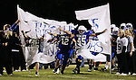 Hunter Robinson, center, and Christian Boyd, right, break through a football banner at senior night at Breathitt County High School on Friday Oct. 14, 2011. The undefeated Bobcats beat the Morgan County Cougars 62-8. Photo by Rachel Aretakis