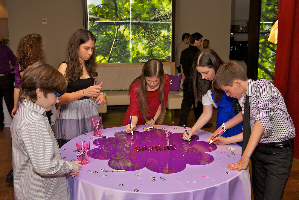 Kids writing on the sign-in table at a Bat Mitzvah celebration.