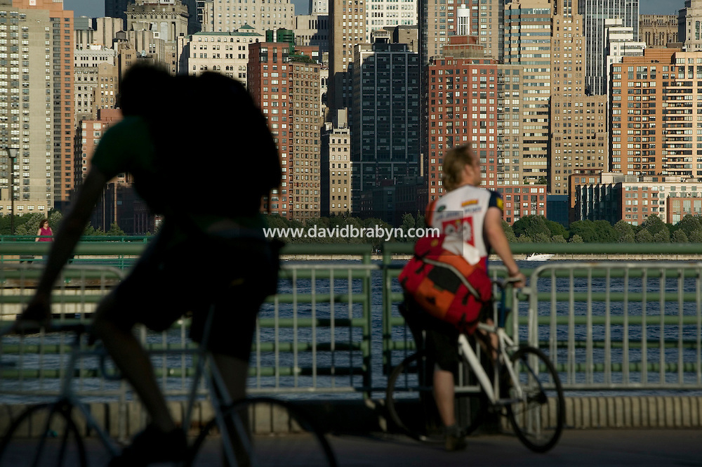 2 July 2005 - Jersey City, NJ, USA - Riders look out at the Manhattan skyline from the Jersey City waterfront at the end of qualifying events for the 13th annual cycle messenger world championships, Jersey City, USA, July 2nd 2005. More than 700 riders from all over the world took part in the 4-day competition which carries event based on the daily work of a city bike messenger.