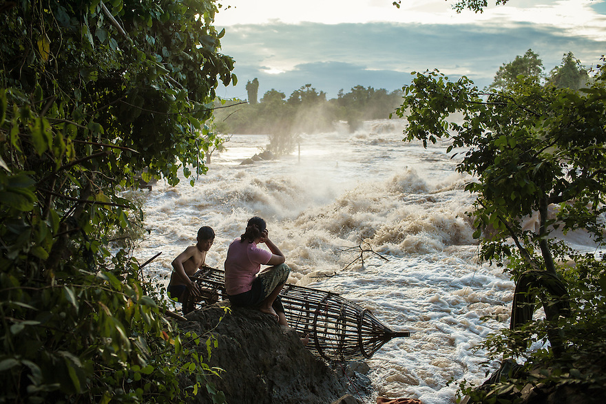 """A fisherman fixes and cleans a """"Ly Trap"""" (a traditional bamboo made trap) in front of the Khone Phapheng falls as his wife watches. 04/08/2013 © Thomas Cristofoletti / Ruom"""