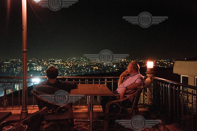 Two men sitting at a table on a rooftop terrace bar enjoy a view over the Golden Horn while smoking a cigarette.