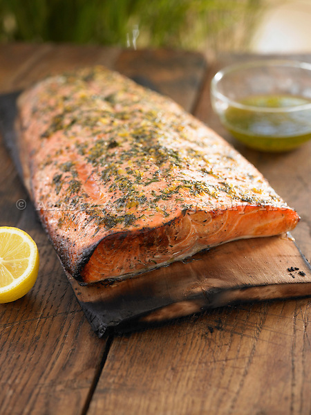 Grilled fillet of salmon on an alder plank. Seen with lemon half and bowl of seasoned oil.