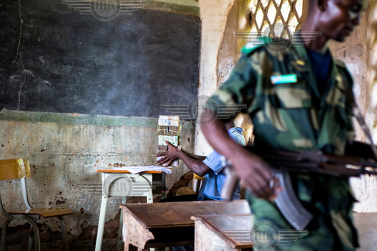 A soldier stands gusrd as a Trust Merchant Bank (TMB) staff member prepares the accounts before paying a civil servants their salaries. A team from the bank took to the road for several weeks to travel the remote region in order to pay state employees and civil servants, mainly teachers, on site.