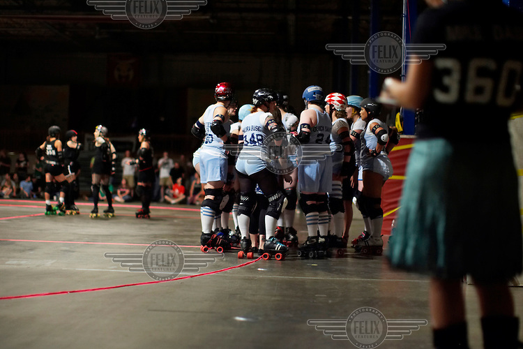 Skaters huddle for a timeout during a roller derby bout in Wilmington, Massachusetts. Roller derby is an American contact sport, popular with young women, which combines both athleticism and a satirical punk third-wave feminism aesthetic.
