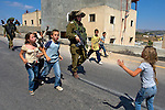 Young Palestinian children jeer at an Israeli army officer following the pursuit of stone throwing Palestinian youths into the West Bank village of Nabi Saleh near Ramallah on 02/07/2010.