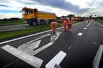 GELDERMALSEN - Op de provinciale weg N237 brengen medewerkers van Heijmans Wegenbouw pijlen aan op het nog warme asfalt tijdens wegwerkwerkzaaamheden op de kruising bij de afslag A2. Hoewel het werk er schijnbaar ongevaarlijk uitziet, werkt de figuratieploeg met gloeiend hete wegverf die meer dan kokend heet is: 180 graden Celcius. De mannen werken daarom meestal met lange mouwen en dragen handschoenen met leren stukken. Omdat de wagen nog niet op het warme asfalt kan rijden, moeten de sjablonen zelf af en toe naar de juiste plaats versleept worden. Behalve het vervangen van het wegdijk, en markeren met strepen, zijn tevens nieuwe detectielussen aangebracht. COPYRIGHT TON BORSBOOM