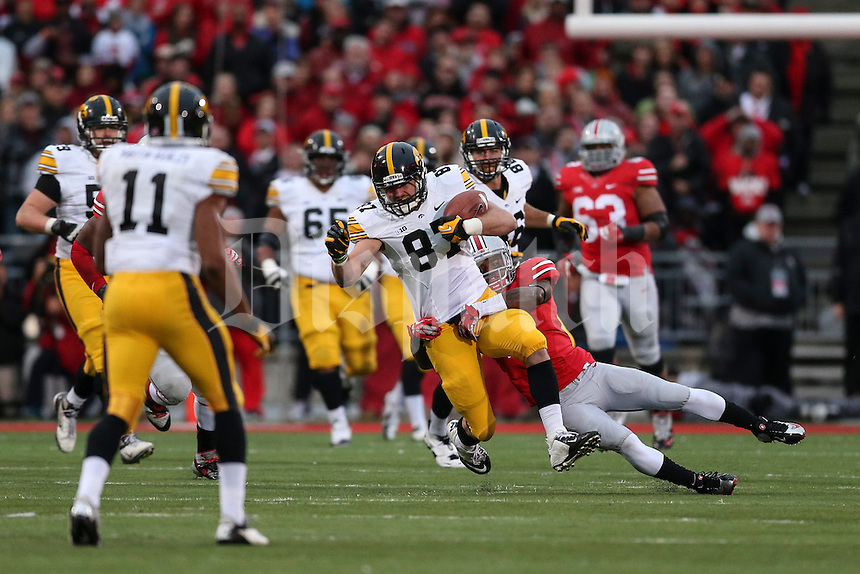 Iowa Hawkeyes tight end Jake Duzey (87) is brought down by Ohio State Buckeyes safety C.J. Barnett (4) during Saturday's game in Columbus, Ohio on Saturday, Oct. 19, 2013. (Jabin Botsford / The Columbus Dispatch)