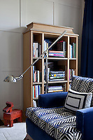 A blue and white patterned armchair and freestanding bookcase in the wood panelled living room