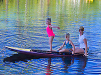 A mom and her two girls float on a standup paddleboard as part of a SUP lesson during a beautiful day at Richardson's Ocean Park, Hilo, Big Island.