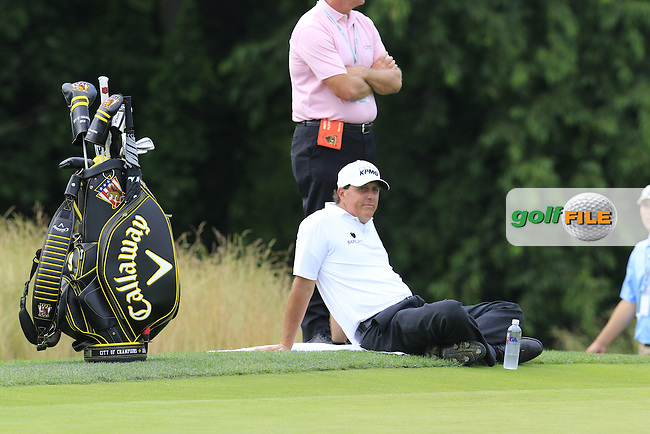 A chill Phil Mickelson (USA) relaxes as ground staff mow the 15th green during Wednesday's Practice Day of the 2016 U.S. Open Championship held at Oakmont Country Club, Oakmont, Pittsburgh, Pennsylvania, United States of America. 15th June 2016.<br /> Picture: Eoin Clarke | Golffile<br /> <br /> <br /> All photos usage must carry mandatory copyright credit (&copy; Golffile | Eoin Clarke)