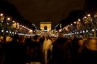 People gather for New Year's Eve celebrations in Champs-Élysées, by the Arc de Triomphe, Paris, France
