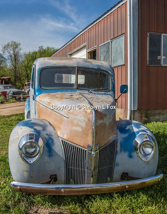 An old blue truck sits in a field in Missouri